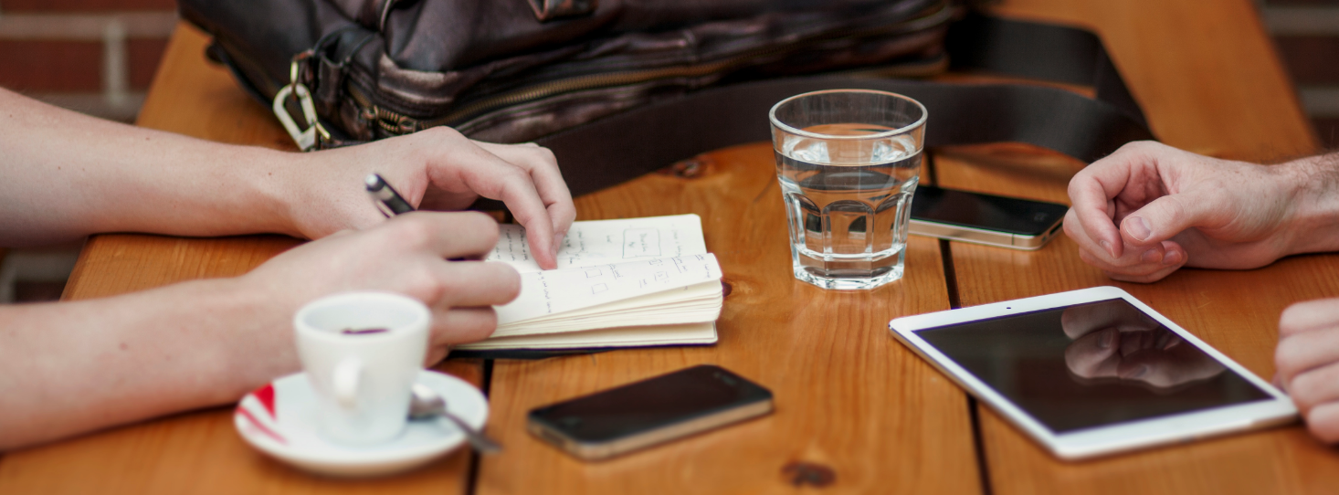 two people have a meeting with phones and tablets on table